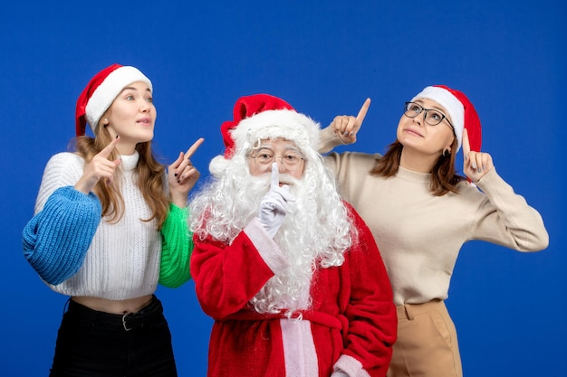 Vorderansicht weihnachtsmann mit weibchen auf einem blauen kalten weihnachtsgefühl schnee neues jahr