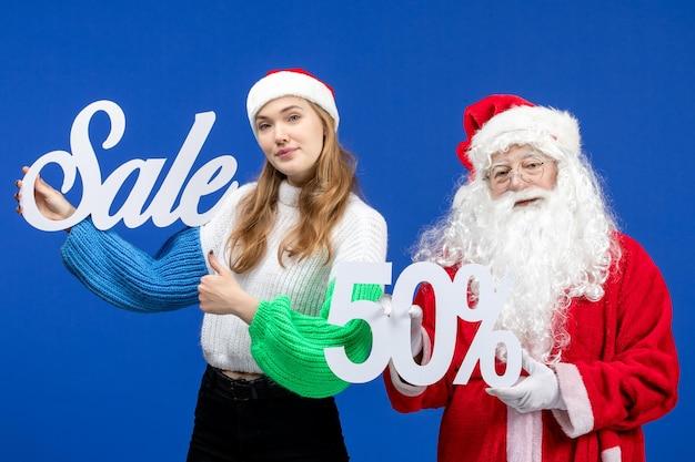 Vorderansicht weihnachtsmann mit weiblichen halten verkaufsschriften an blauen ferien kalten weihnachten neujahr schnee einkaufen