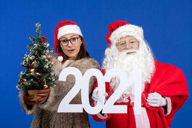 Vorderansicht weihnachtsmann mit weiblicher holdingschrift und kleinem weihnachtsbaum auf blauem neujahr