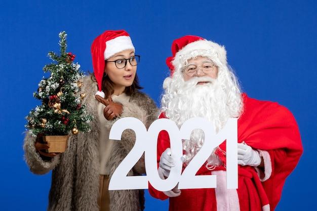 Vorderansicht weihnachtsmann mit weiblicher holdingschrift und kleinem weihnachtsbaum auf blauem neujahrsfest