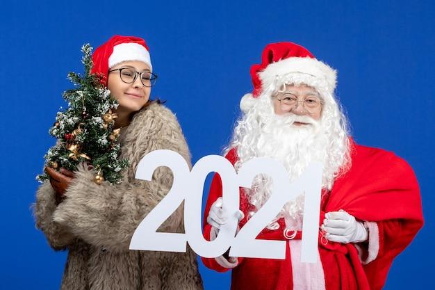 Vorderansicht weihnachtsmann mit weiblicher holdingschrift und kleinem weihnachtsbaum auf blauem neujahrsurlaub