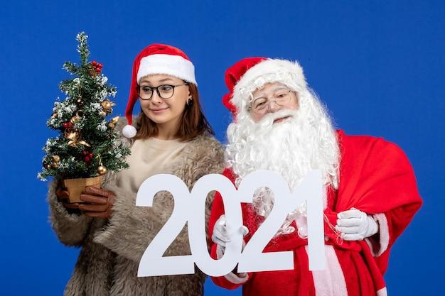 Vorderansicht weihnachtsmann mit weiblicher holdingschrift und kleinem weihnachtsbaum auf blauer neujahrsfarbe