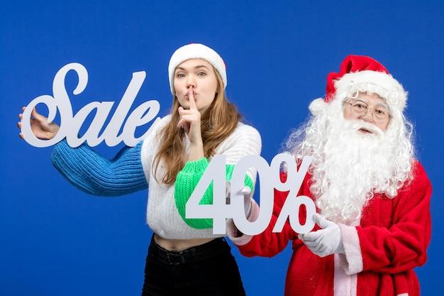 Vorderansicht weihnachtsmann mit weiblicher verkaufsschrift auf dem blauen weihnachtsweihnachtsschnee des neuen jahres