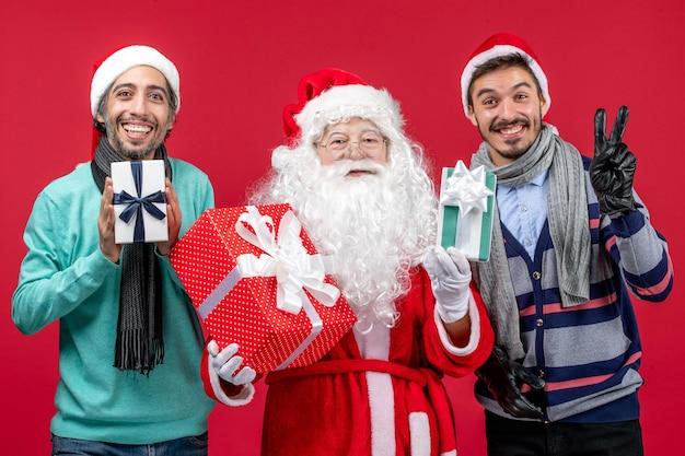 Vorderansicht weihnachtsmann mit zwei männern, die geschenke auf dem roten emotion roten neujahrsgeschenk weihnachten halten