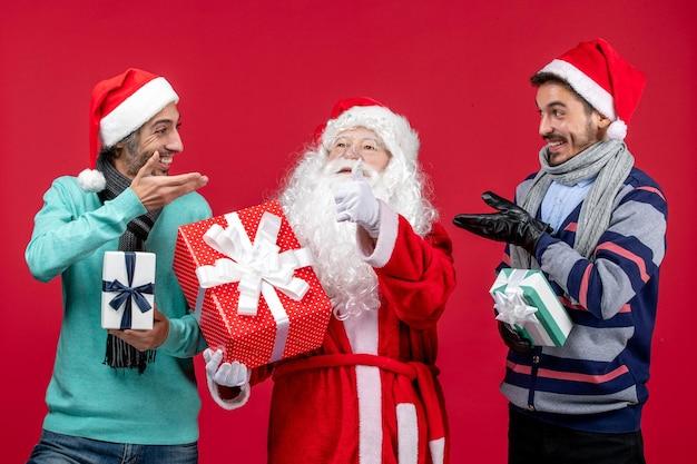 Vorderansicht weihnachtsmann mit zwei männern, die geschenke auf rotem boden neues jahr geschenk emotion weihnachten halten