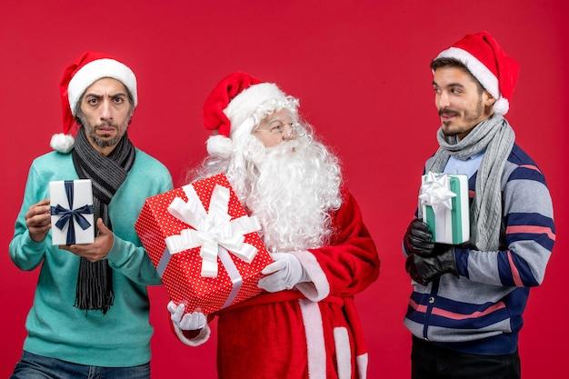Vorderansicht weihnachtsmann mit zwei männern, die geschenke auf rotem geschenkgefühl weihnachten neues jahr rot halten