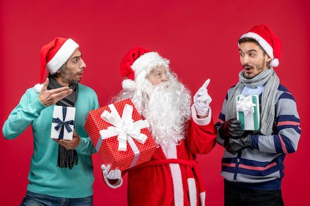 Vorderansicht weihnachtsmann mit zwei männern, die geschenke auf rotem neujahrsgeschenk emotion weihnachtsrot halten