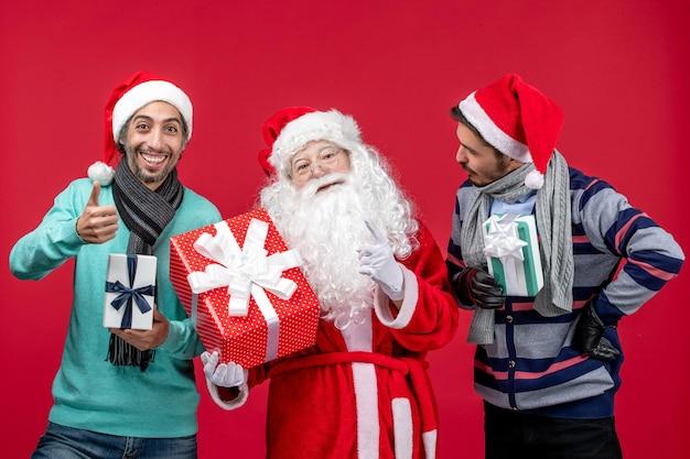 Vorderansicht weihnachtsmann mit zwei männern, die geschenke auf rotem neujahrsgeschenk emotionen weihnachten rot halten