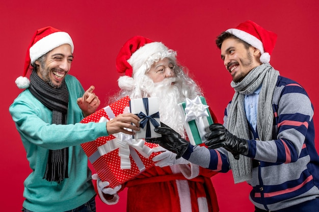 Vorderansicht weihnachtsmann mit zwei männern, die geschenke auf rotem rotem neujahrsgeschenk gefühle weihnachten halten