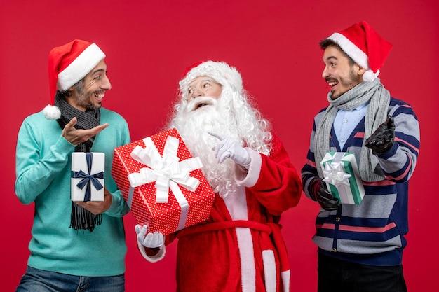 Vorderansicht weihnachtsmann mit zwei männern, die geschenke auf rotem schreibtisch halten neujahrsgeschenk emotion weihnachten rot