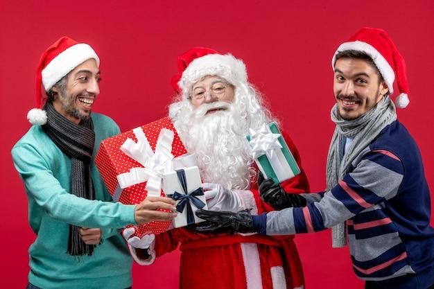 Vorderansicht weihnachtsmann mit zwei männern, die geschenke auf rotem schreibtisch halten rotes neujahrsgeschenk emotion weihnachten