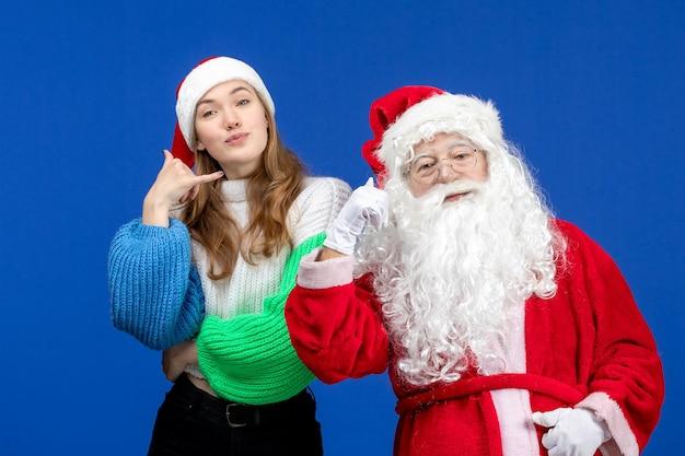 Vorderansicht weihnachtsmann zusammen mit jungen frauen, die auf blauem neujahrsurlaub weihnachten kalten schnee stehen