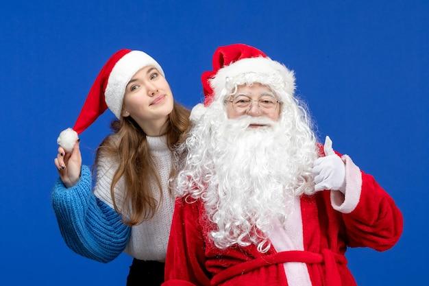 Vorderansicht weihnachtsmann zusammen mit junger frau auf blauem menschenweihnachtsfarbe neujahrsurlaub