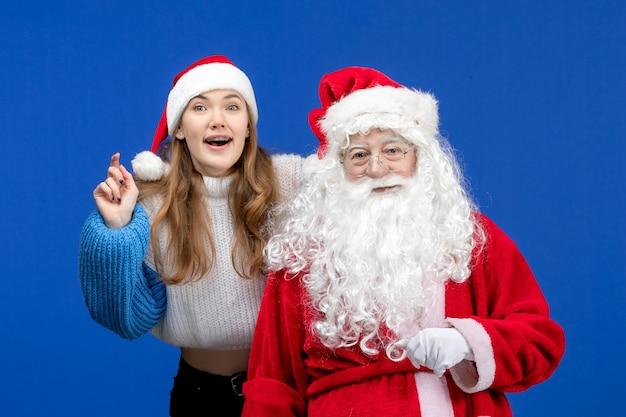 Vorderansicht weihnachtsmann zusammen mit junger frau auf blauem urlaub menschliche weihnachtsfarbe