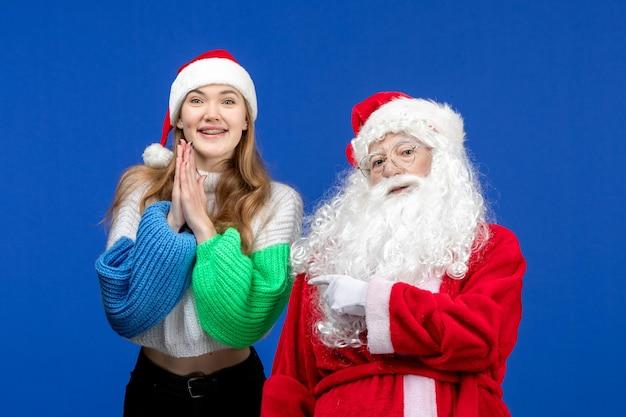 Vorderansicht weihnachtsmann zusammen mit junger frau auf blauem urlaub menschliche weihnachtsfarben neues jahr