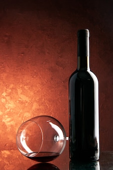 Vorderansicht-weinglas mit einer flasche wein auf dunklem champagner-weihnachtsalkoholgetränk