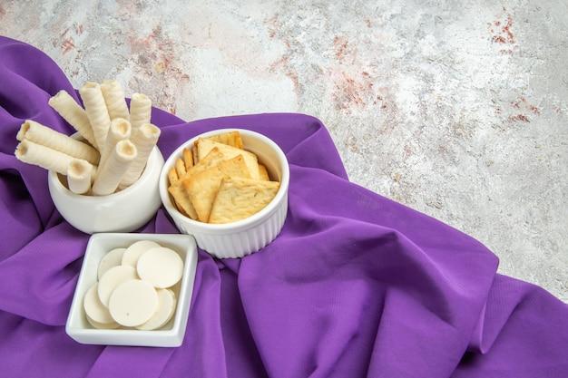 Vorderansicht weiße bonbons mit crackern auf einem violetten tissue-farbbonbonbonbon
