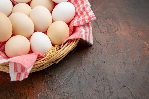 Vorderansicht weiße hühnereier im korb mit handtuch auf dunkler oberfläche