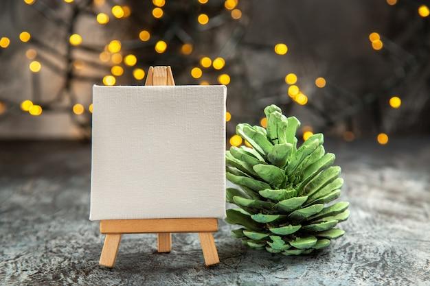 Vorderansicht weiße leinwand auf holz staffelei weihnachtslichter grüner tannenzapfen auf dunklem hintergrund