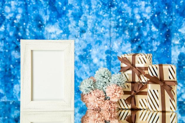 Vorderansicht weißer fotorahmen weihnachtsgeschenke blumen reflektiert auf spiegel mit blauem galaxie hintergrund