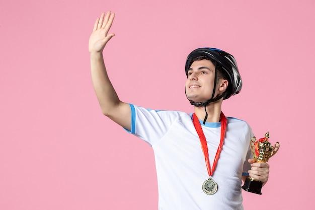 Vorderansicht winkender männlicher athlet in sportkleidung, die goldenen becher mit helm hält