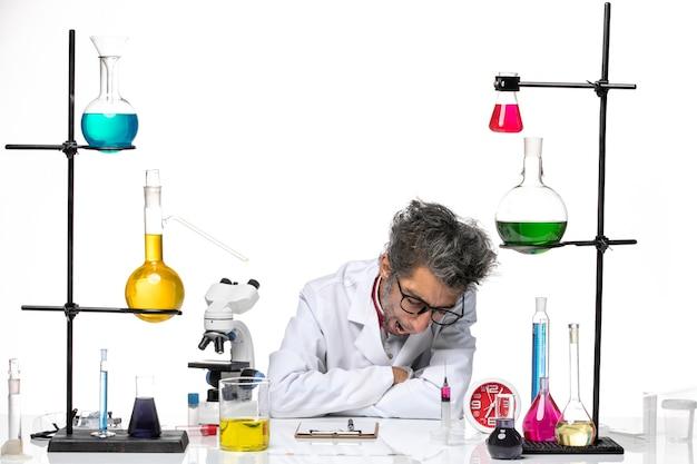 Vorderansicht wissenschaftler mittleren alters im gähnenden weißen medizinischen anzug