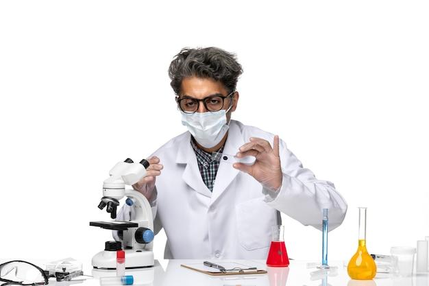 Vorderansicht wissenschaftler mittleren alters im medizinischen anzug, der kleine probe durch mikroskop prüft