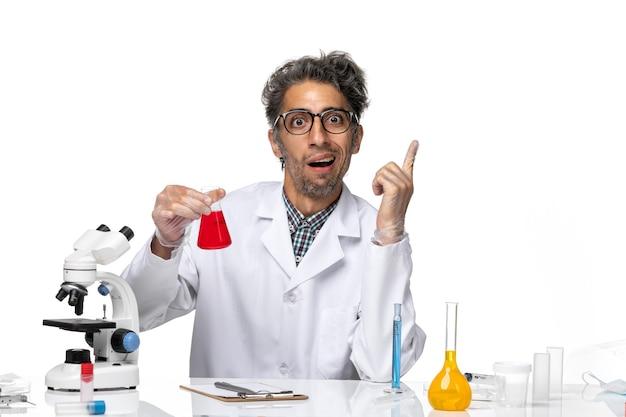 Vorderansicht wissenschaftler mittleren alters im medizinischen anzug mit roter lösung