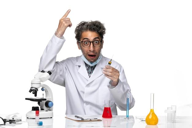 Vorderansicht wissenschaftler mittleren alters im weißen medizinischen anzug, der die injektion vorbereitet