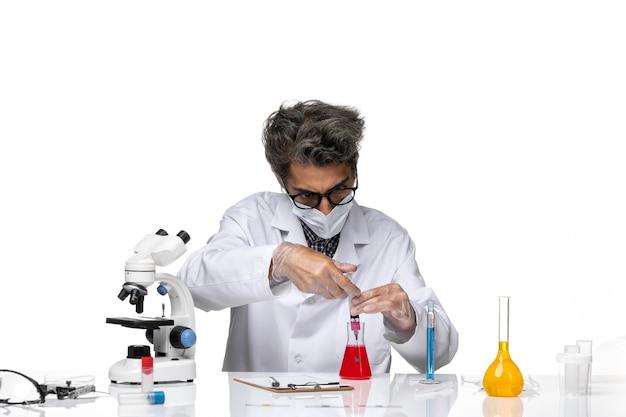 Vorderansicht wissenschaftler mittleren alters im weißen medizinischen anzug, der injektion mit lösung füllt