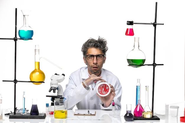 Vorderansicht wissenschaftler mittleren alters im weißen medizinischen anzug, der uhren hält