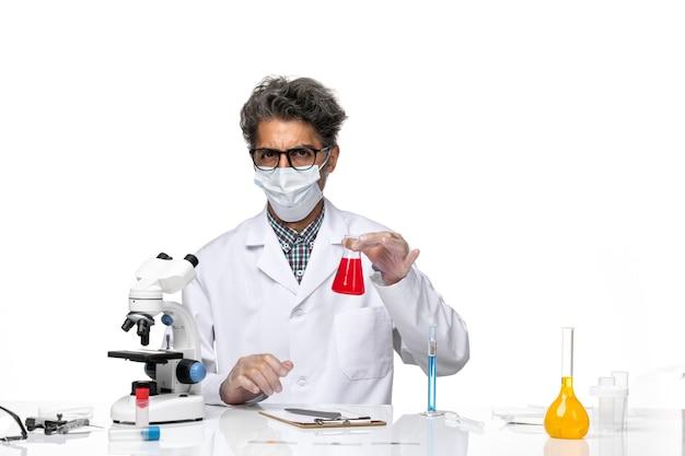 Vorderansicht wissenschaftler mittleren alters in spezialanzug sitzend mit flasche mit roter lösung