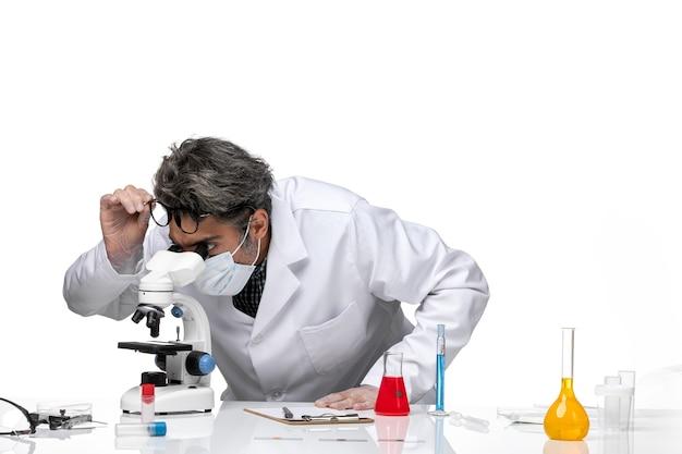 Vorderansicht wissenschaftler mittleren alters in speziellem weißen anzug unter verwendung eines mikroskops