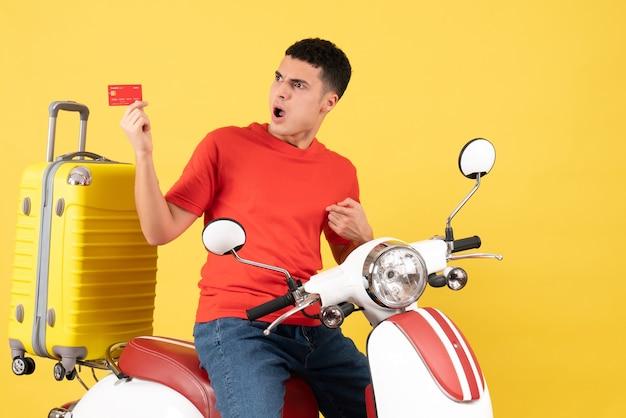 Vorderansicht wunderte sich junger mann auf moped, der rabattkarte hält