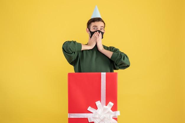 Vorderansicht wunderte sich junger mann mit partykappe, die hinter großer geschenkbox auf gelb steht