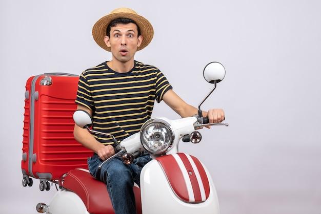Vorderansicht wunderte sich junger mann mit strohhut auf moped, der kamera betrachtet