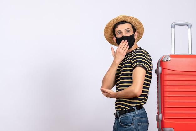 Vorderansicht wunderte sich junger tourist mit schwarzer maske, die in der nähe des roten koffers steht