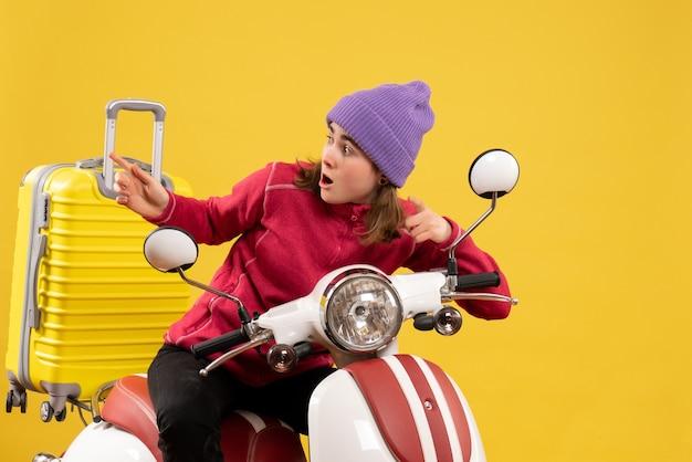Vorderansicht wunderte sich junges mädchen auf moped, das auf etwas zeigte