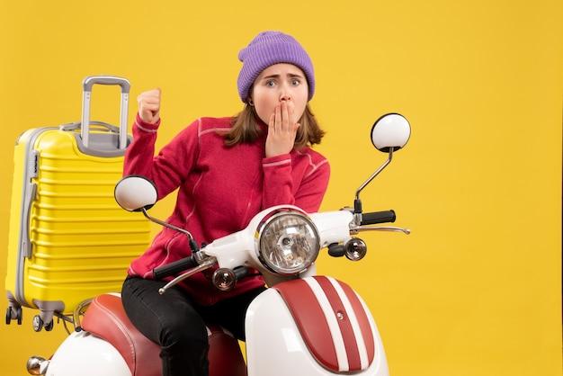 Vorderansicht wunderte sich junges mädchen auf moped, das auf ihren koffer zeigte