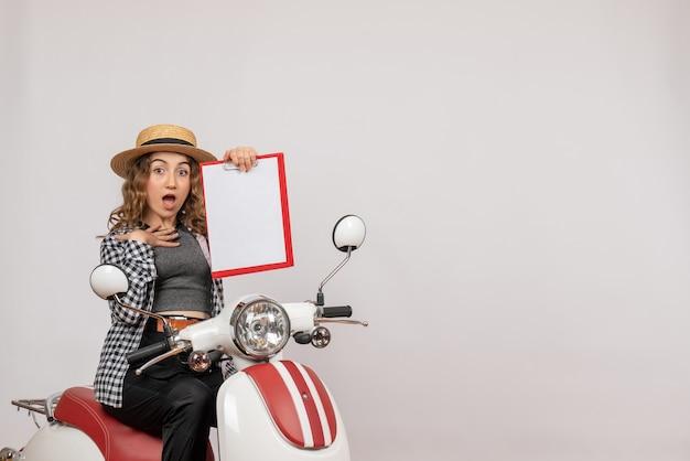 Vorderansicht wunderte sich junges reisendes mädchen auf moped mit rotem klemmbrett
