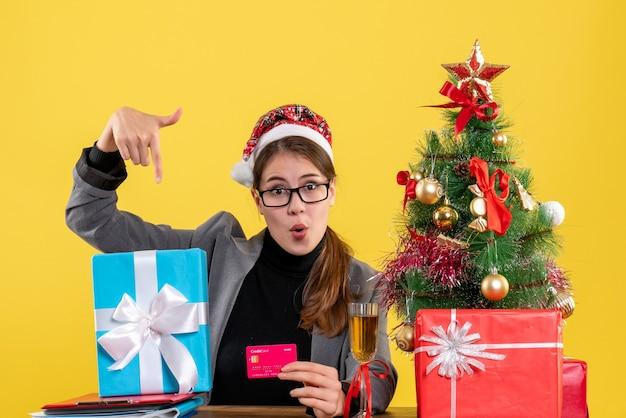 Vorderansicht wunderte sich mädchen mit weihnachtshut, das am tisch hält, der weihnachtsbaum der karte und geschenkcocktail hält