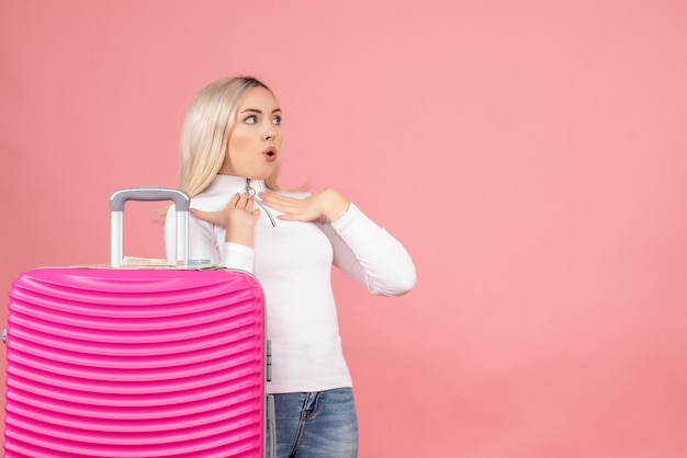 Vorderansicht wunderte sich schöne frau mit rosa koffer, die etwas ansah