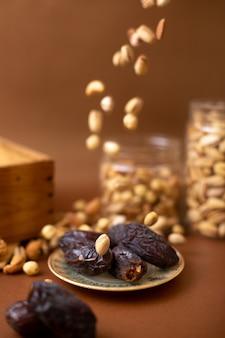 Vorderansicht xurma und erdnüsse auf der braunen holzoberfläche