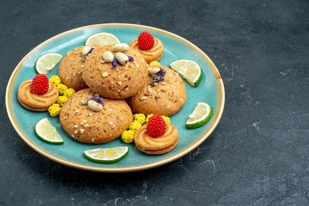 Vorderansicht-zuckerplätzchen mit frischen zitronenscheiben auf süßem kuchen des grauen oberflächenkuchenplätzchenkekses