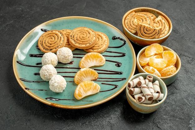 Vorderansicht-zuckerplätzchen mit kokosnussbonbons auf dem grauen tischkeksplätzchen süß