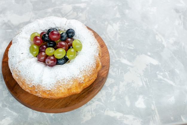 Vorderansicht zuckerpulver kuchen köstlich gebackenen kuchen mit frischen trauben auf dem weißen schreibtisch obst backen kuchen keks zucker süß