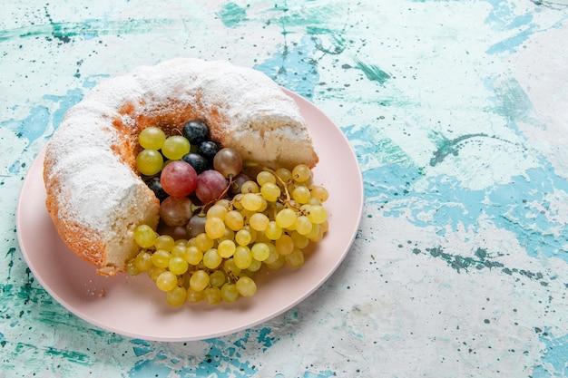 Vorderansicht zuckerpulver kuchen köstlich geschnitten mit frischen trauben auf hellblauer oberfläche obstkuchen backen zucker süße keksteigpastete