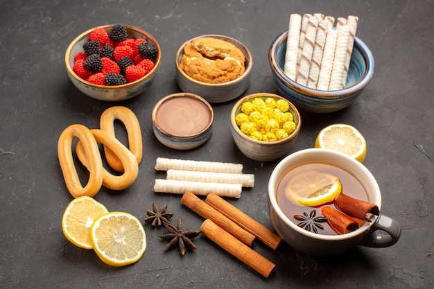 Vorderansicht zuckersüßigkeiten mit tasse tee und keksen auf dunklem hintergrund süßer süßigkeitskeks-keks-tee