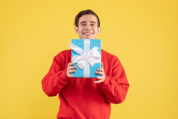 Vorderansicht zufriedener junger mann mit rotem pullover, der geschenk auf gelb zeigt