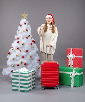 Vorderansicht zufriedenes junges mädchen, das weihnachtsmannmütze steht, das nahe weihnachtsbaum und geschenke steht